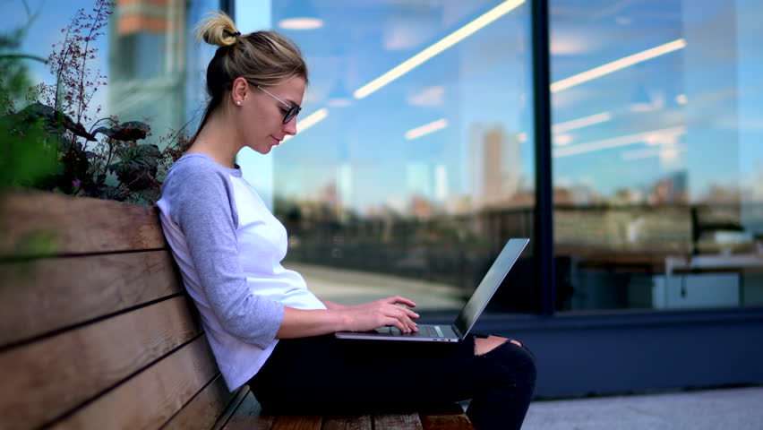 Skilled student typing text on keyboard of laptop device and thinking on continuation of coursework sitting on territory of campus.Female office worker chatting on netbook outdoors  | Shutterstock HD Video #33980470