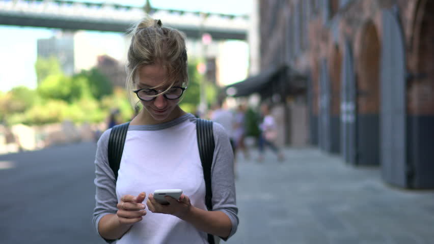 Cheerful female tourist in eyeglasses installing navigator on modern telephone device walking on streets in urban setting.positive traveller strolling and publishing new post on website