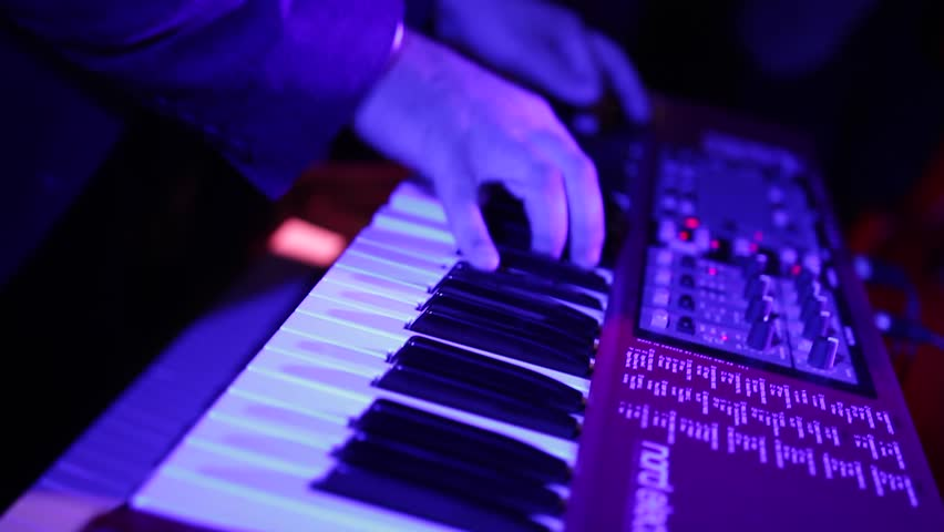 Male hands playing electric piano under colorful stage lighting, close-up. Musician in a suit perform a composition on a keyboard music workstation on a party night.