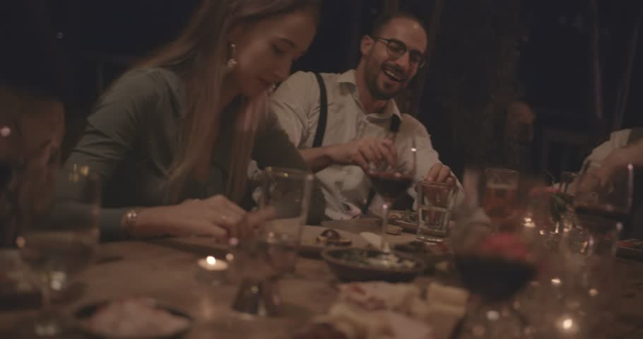 Young elegant friends on mediterranean summer holidays having fun at rustic dinner party in countryside