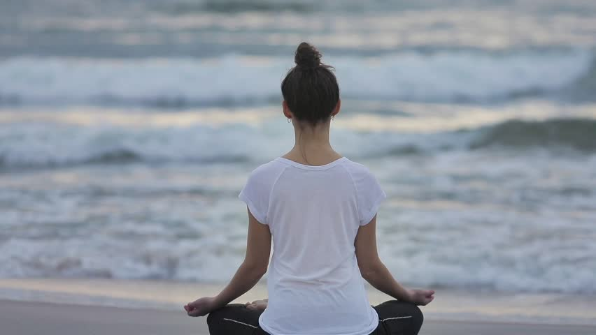 Woman meditates on beach sitting in lotus position slow motion back to camera morning or evening sunset. Waves rolling to no face girl in Buddha asana pose close up. Meditation in sukhasana on seaside