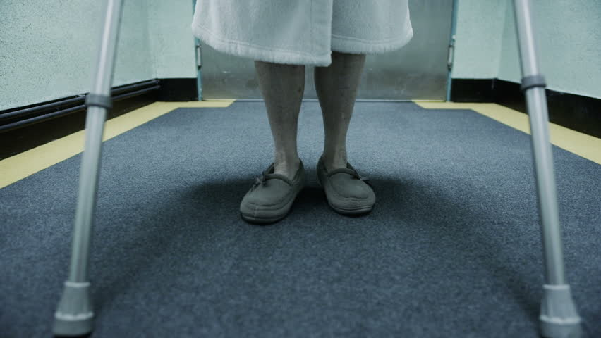 Floor level shot of an elderly lady's feet. She is struggling to walk and is assisted by crutches. In slow motion.