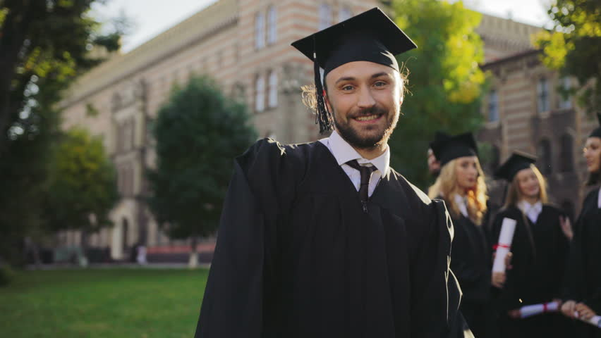 Cheerful attractive male graduate standing in front of the camera and giving his thumb up. Graduates on the background. Outdoors. Portrait shot
