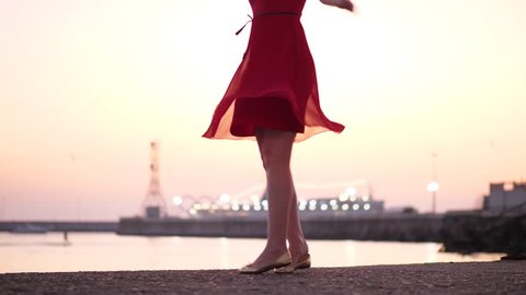 Happy young adult woman spinning around on bank against evening sea and port, low view. Light dress skirt fly round, merry girl dance in high spirits. Blurred cruise ship lights seen on background