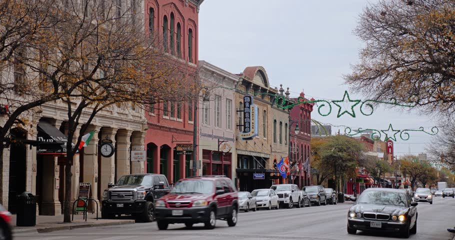AUSTIN, TX - Circa December, 2017 - Traffic passes bars and restaurants on E 6th Street in Austin's historic tourist district on an overcast day. Day/night matching available.