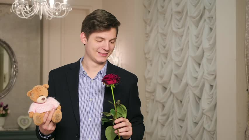 Portrait waiting man in black business suit with red rose and cute teddy bear to give girl on romantic date looking at camera on background light curtains on window in a living room | Shutterstock HD Video #34052116