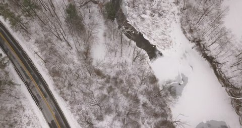 drone tracking shot flying over a frozen river: winter landscape, trees, stream, river looking straight down