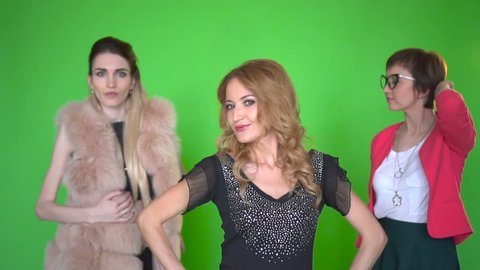 Three beautiful young women in stylish clothes dan?ing at camera on green screen background. Chroma key