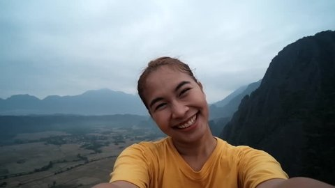 Cheerful enthusiastic Asian tourist girl turn around in Pha Ngeun, Vang Vieng, Laos. Young woman have fun and happy sightseeing on the top of mountain with beautiful landscape and nature. Selfie shot.