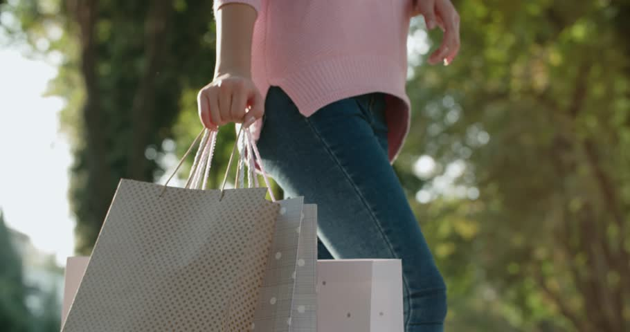 close-up hand girl with shopping bags walking by the street, Steadicam shot
