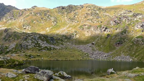 """Landscape with lake. View of """"Creussans"""" lake in Ordino, Andorra, with a slow upward movement and two tiny and unrecognizable people fishing at the bottom."""