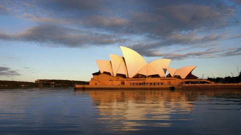Sydney Opera House, a World Heritage site and a masterpiece of 20th-century architecture at sunset with calm water, HD1080p
