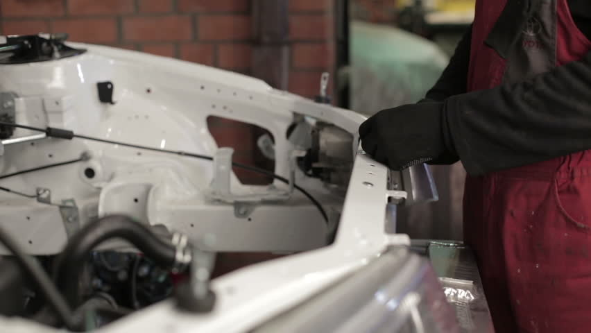 The mechanic works on rebuilding of sport rally car.
