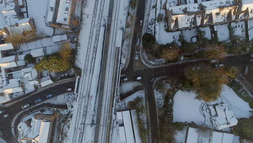 Bird's Eye View of a Commuter Train Departing a Railway Station in the Snow #34153816