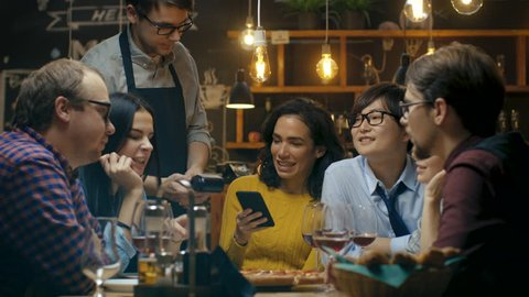 In the Bar Waiter Holds Credit Card Payment Machine and Beautiful Woman Pays for Her Order with Contactless Mobile Phone Payments System. She's Surrounded by Dear Friends and Has Time of Her Life. Sho
