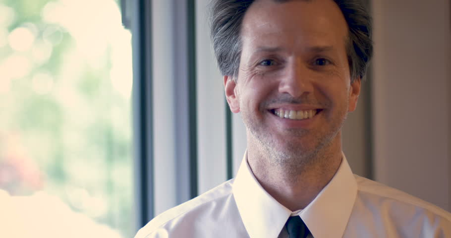 Portrait of attractive man with a shirt and tie nodding and smiling while looking at the camera - copy space