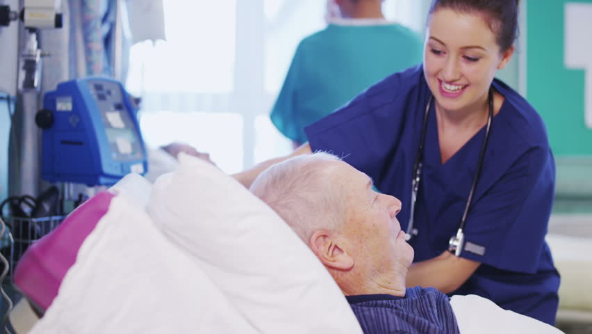 A beautiful female nurse attends to an elderly male patient, plumping up his pillows and chatting with him. In slow motion.  | Shutterstock HD Video #3421832