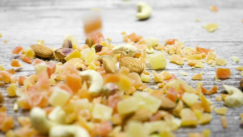 Slow motion of Healthy type of nuts and sweet on wooden background. Dry healthy snack food