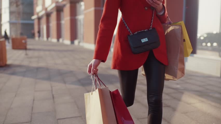 Attractive young woman spend some money, and carries lots of shopping bags, using her smartphone at the same time. Cheerful mood, positive emotions, true happiness.   Shutterstock HD Video #34243606