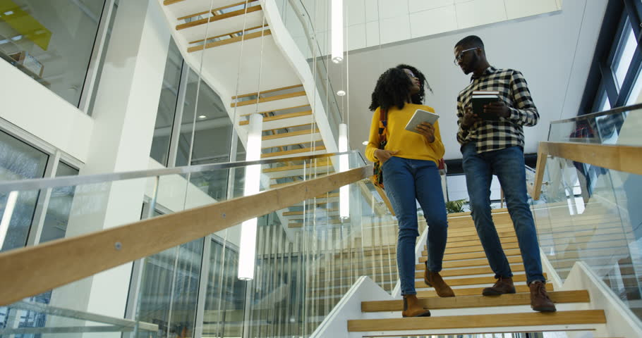 Young African American couple of students going down the stairs at the college after the classes and talking. Man asking a woman about a date. Indoor