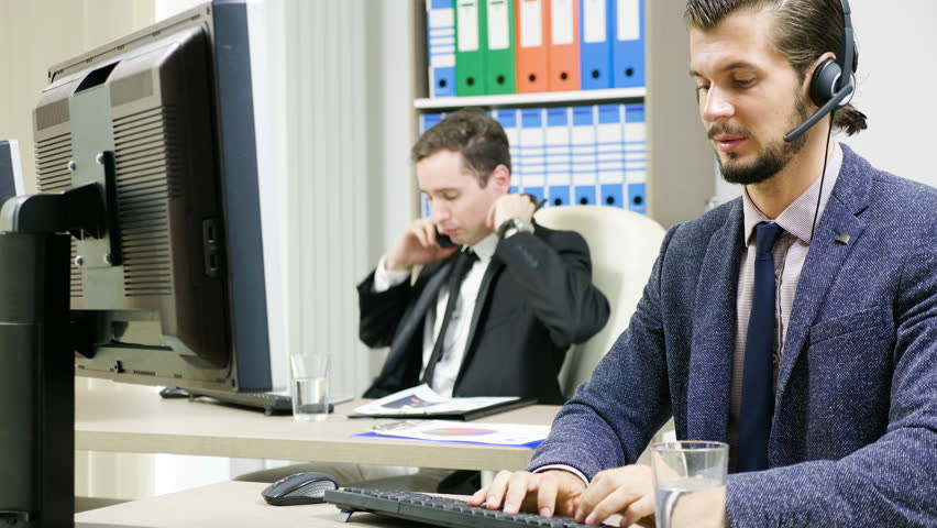 Company workers in suit using headset to talk on the hot line with customers | Shutterstock HD Video #34246096