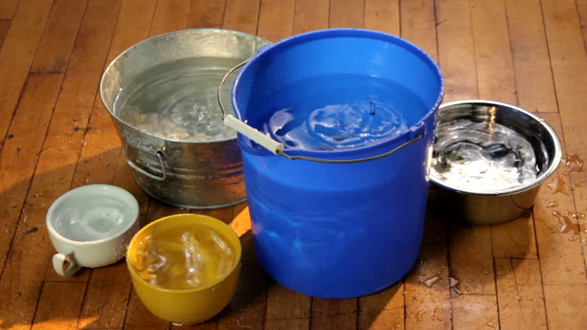 Water dripping from a leaking ceiling into colorful buckets and containers on