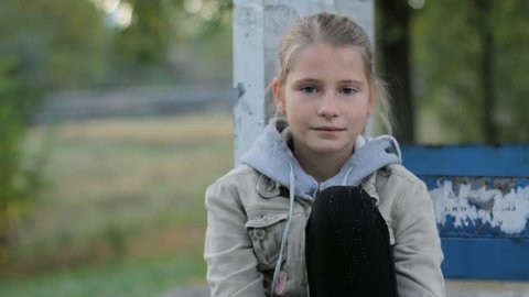 Pretty preteen girl child calm looking at camera sitting alone outdoors
