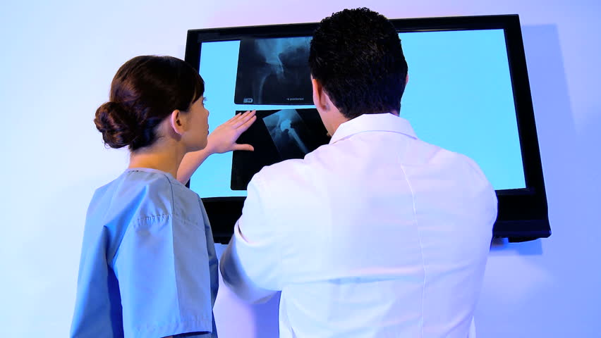 Training doctor & medical student examine patient x-rays