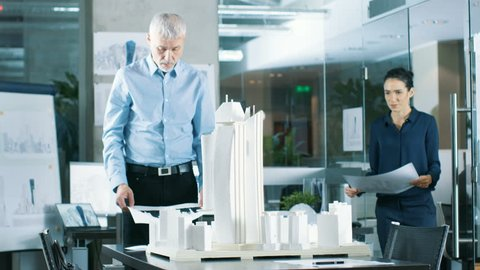In the Architectural Bureau Female Engineer Brings Blueprints and Shows them to Senior Architect, They Discuss Project. They Work as Urban Planners on a Building Model. Shot on RED EPIC-W 8K Camera.