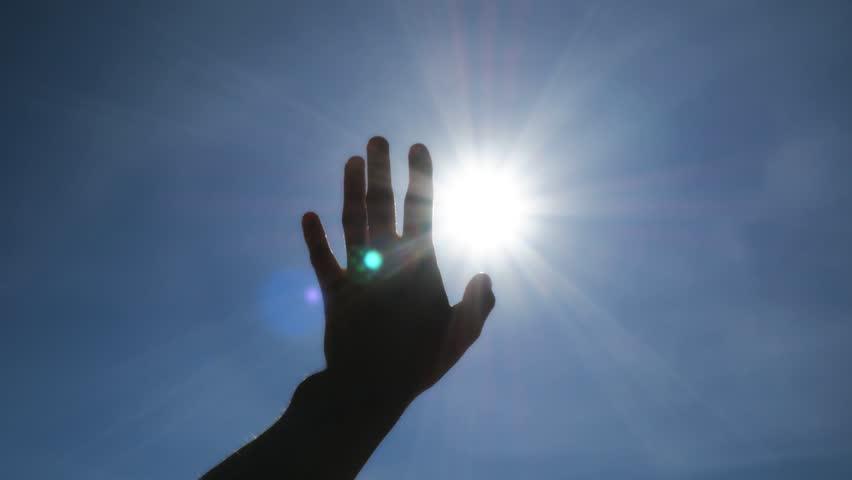 Hand of man strive to sun and deep blue sky. Conceptual scene.