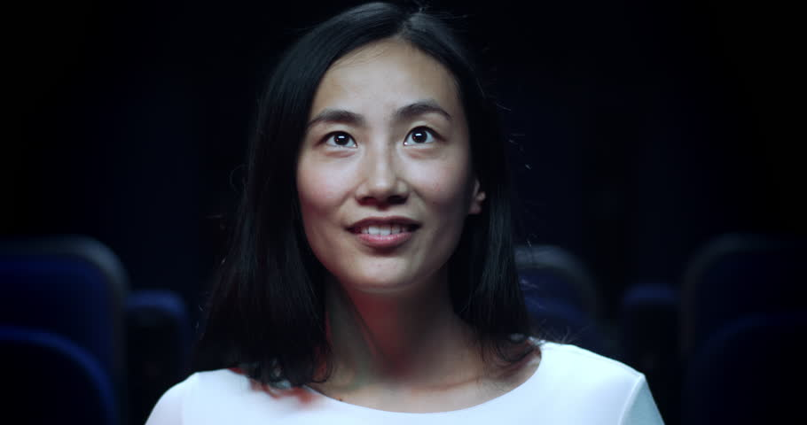 Close up, slow motion shot of an asian woman in a movie theatre reacting in awe.