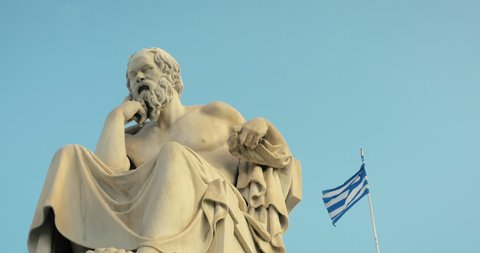 SLOW MOTION: greatest philosopher of Greece Socrates reflects on the meaning of life, on the background of Greek flag.