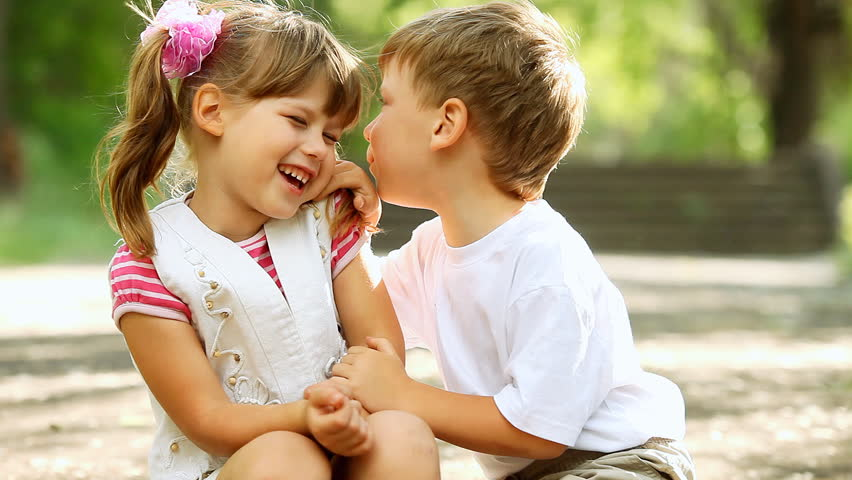 Two children telling secrets and laughing in park, outdoors. dolly shot.