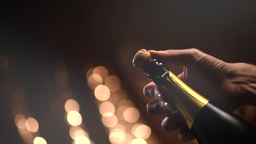 Champagne explosion. Champagne popping, opening champagne bottle closeup. Sparkling Wine over Holiday Bokeh Blinking Background. Party, Success, holiday celebrating. Slow motion UHD 4K