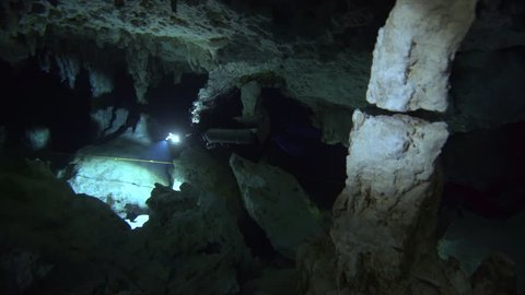 group of divers with flashlights in cenote cave dos ojos