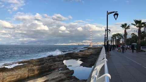 Beirut, Lebanon - 12.25.2017: Pan Right on people strolling on Beirut's seaside corniche, a major outdoor recreation space in the urban capital.