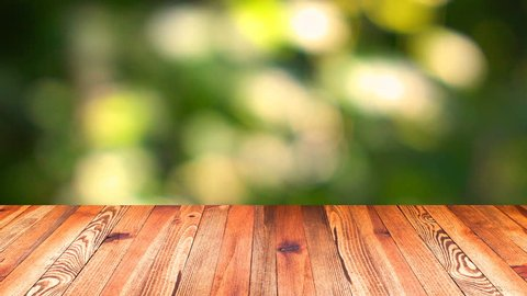 Perspective wood and bokeh light background. product display template. Wood table top on blur moving natural green leaf background.
