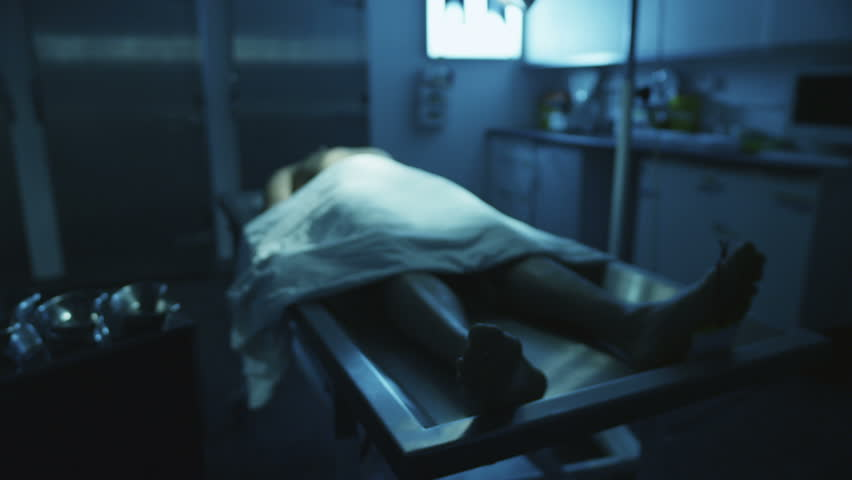 The lifeless naked corpse of a young mixed race male is laid out on the autopsy table, all alone in the dark and with a tag on the toe.