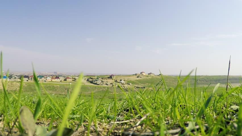 A view on the village and near Yanar Dag through trembling grass in sunny day. Oktober, 2017. Baku, Azerbaijan.