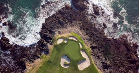 Drone video of waves hitting the rocks on the seashore next to a beautiful golf course