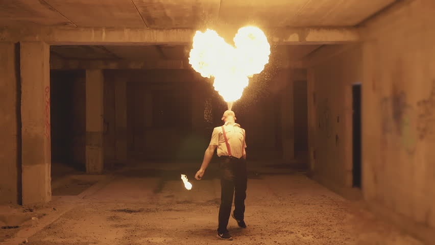 Fire show artist breathe fire in the dark at abandon building, slow motion. Fire in heart shape.