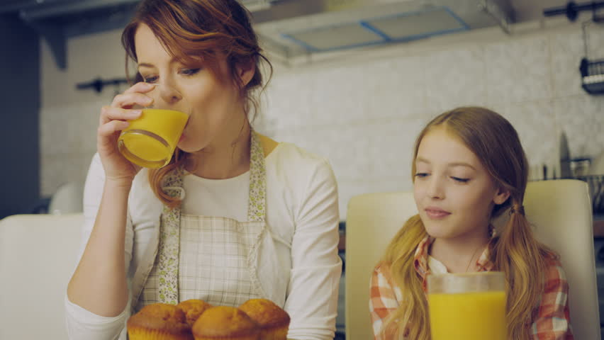 Attractive mother in the apron drinking juice and her cute daughter kissing her in the cheek, than mom and daughter kissing and hugging in the kitchen. Indoors