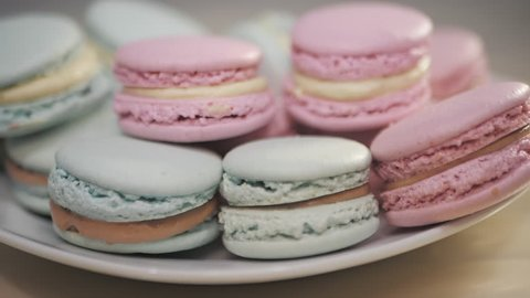 French macarons - meringue cookies with ganache or buttercream filling. Colorful macaroons rotating, horizontal view , slow motion