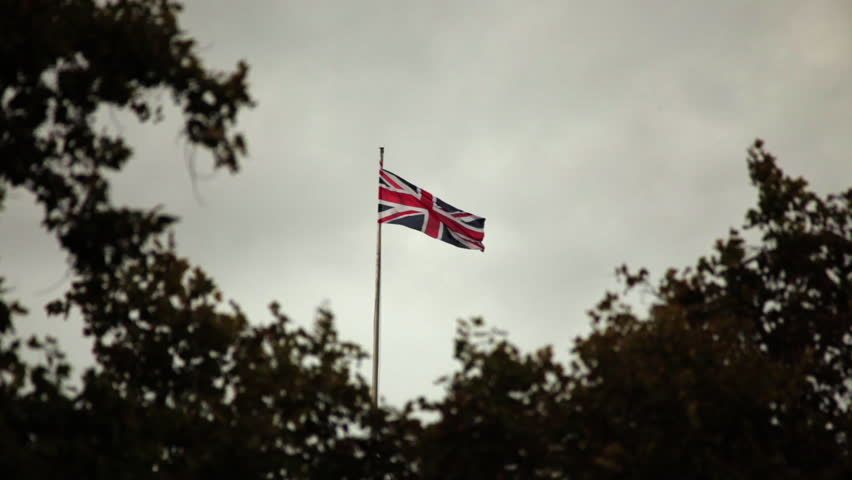 Union Jack waving in London, trees in the foreground.