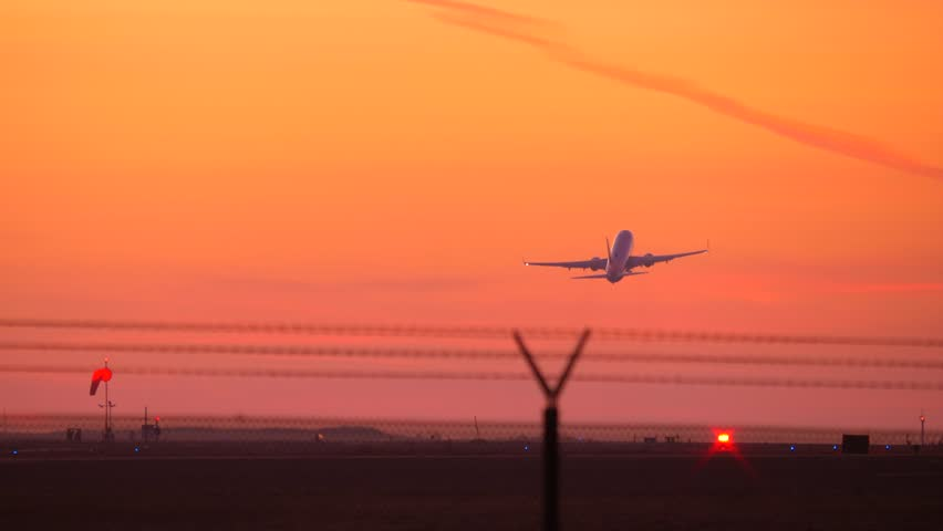 Twin jet engine plane taking off in silhouette against an orange sky sunset from LAX airport with sound.