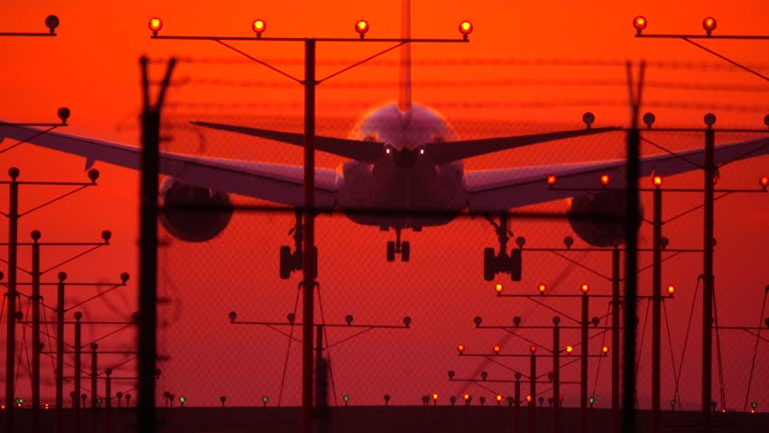 Jet plane landing against a red sunset sky at LAX airport