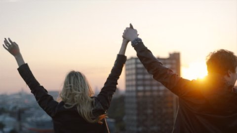 couple in rock n roll style walking on the rooftop and enjoing sunset, close-up raised and waving hands at blue sky background, concept of happy young people slowmotion shot