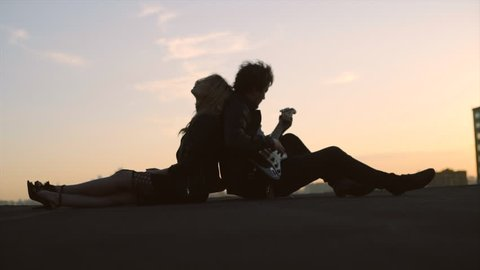 couple in rock-n-roll style siting on the rooftop with flapping hairs on the wind at sunset sky background, man playing on guitar