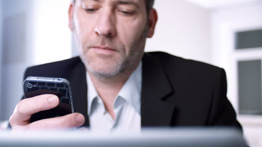 Businessman using his smart phone - tracking shot