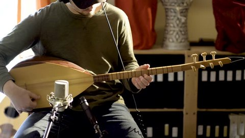 Static shot of young man wearing headphones playing baglama saz with microphones in front of instrument and oud and darbuka drums in background in a room with a lot of light and camera slide to the ri